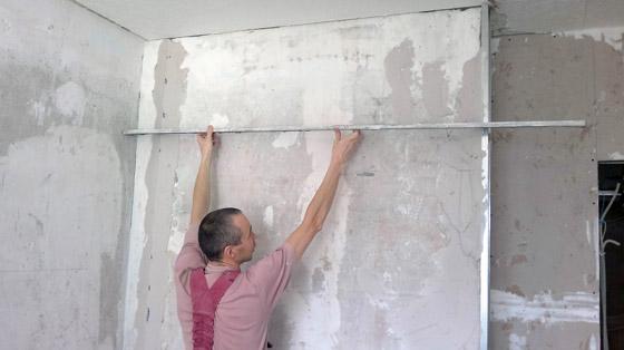 Процесс нанесения стартовой шпаклевки на стену
